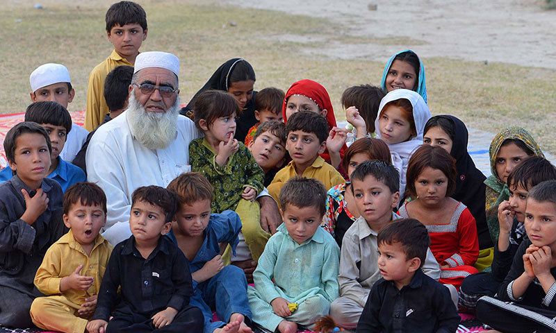 Internally-displaced Pakistani resident Haji Gulzar Khan Wazir (6L), who fled with his family following a military operation against militants in the North Waziristan tribal agency, poses for a photograph with some his children in Bannu. — Photo by AFP