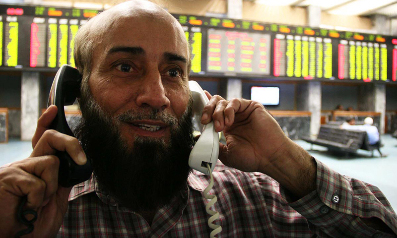 KARACHI: A jubilant stockbroker busy on phone at the KSE on Thursday.—Photo by Online