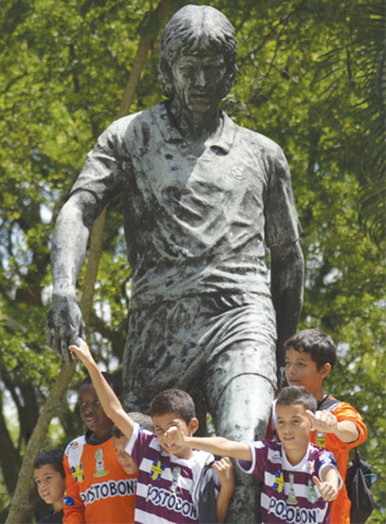 Children with Andres Escobar's statue
