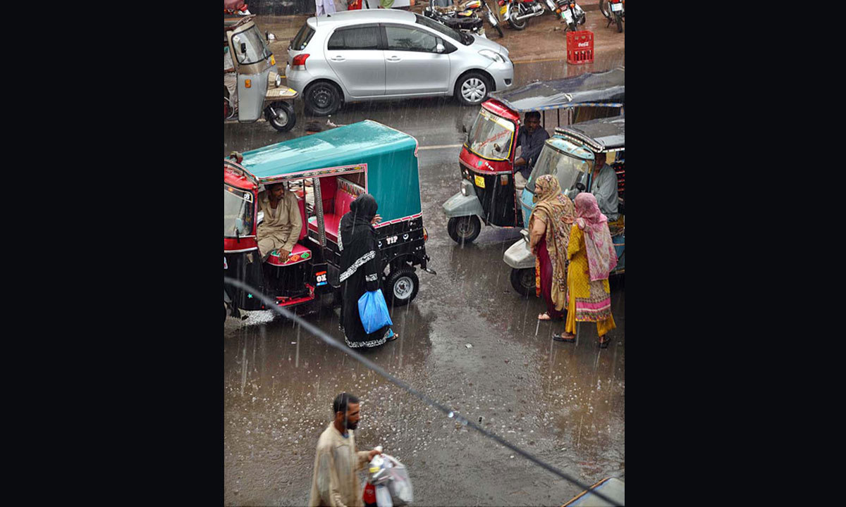 MULTAN: People on their way during rain as weather turned pleasant. — Photo by APP
