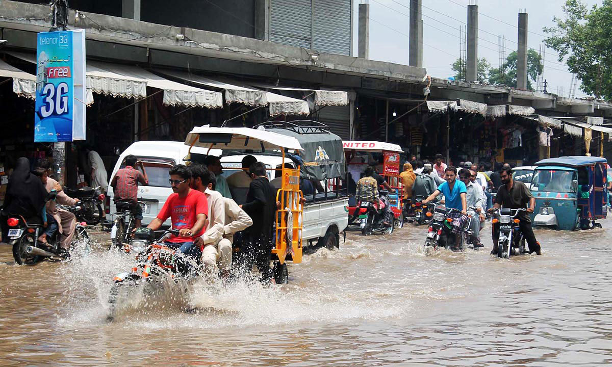 SIALKOT: People facing hardships as they wade through the rainwater accumulated on the road after rain in the city. — Photo by Online