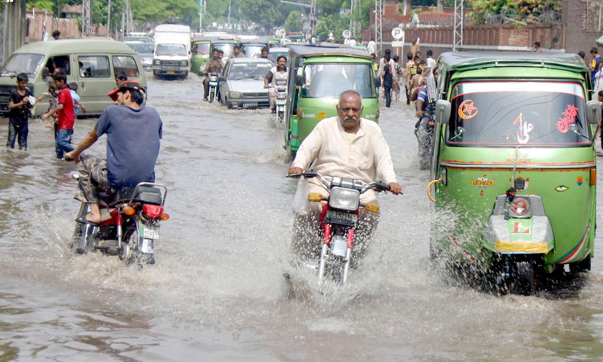 LAHORE: Vehicles passing through the stagnant rainwater after rain. — Photo by INP