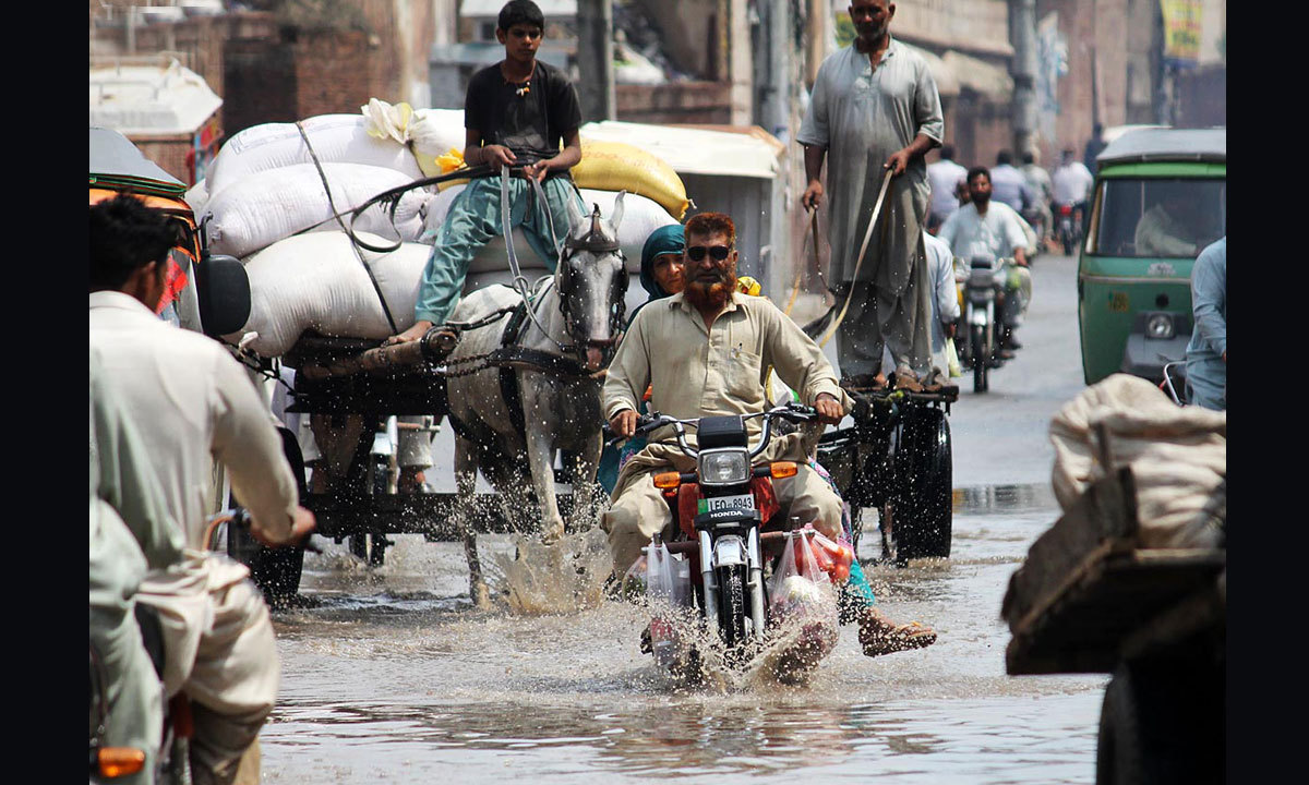 LAHORE: Commuters wade through the rainwater accumulated on the road after rain in Baghbanpura Area. — Photo by Online