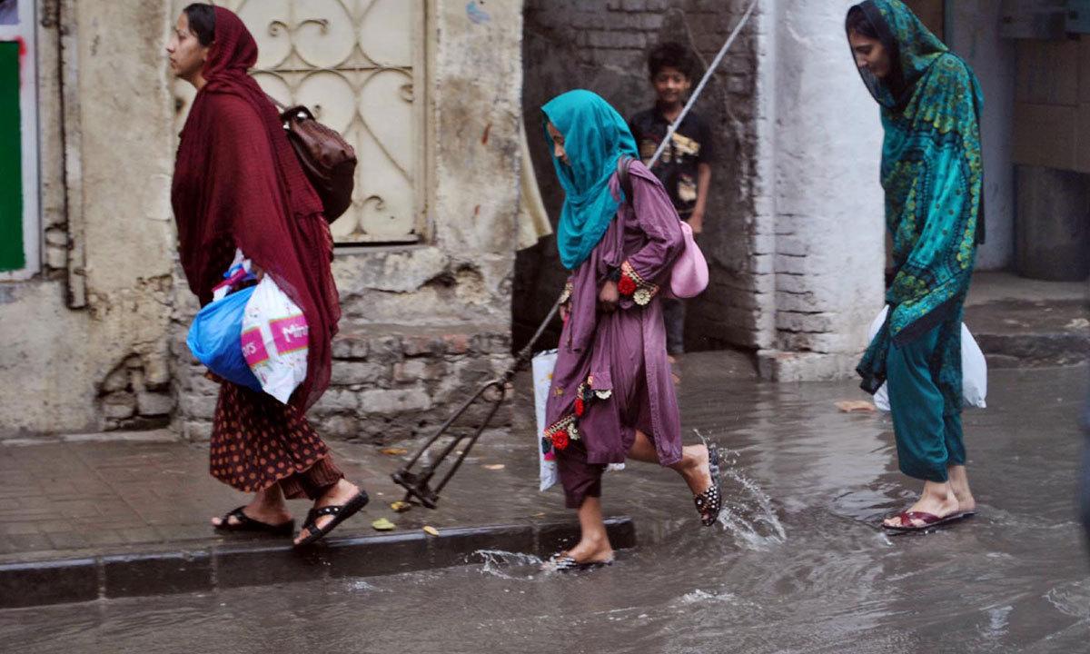 RAWALPINDI: Women passing through the stagnant rain water after rain. — Photo by INP