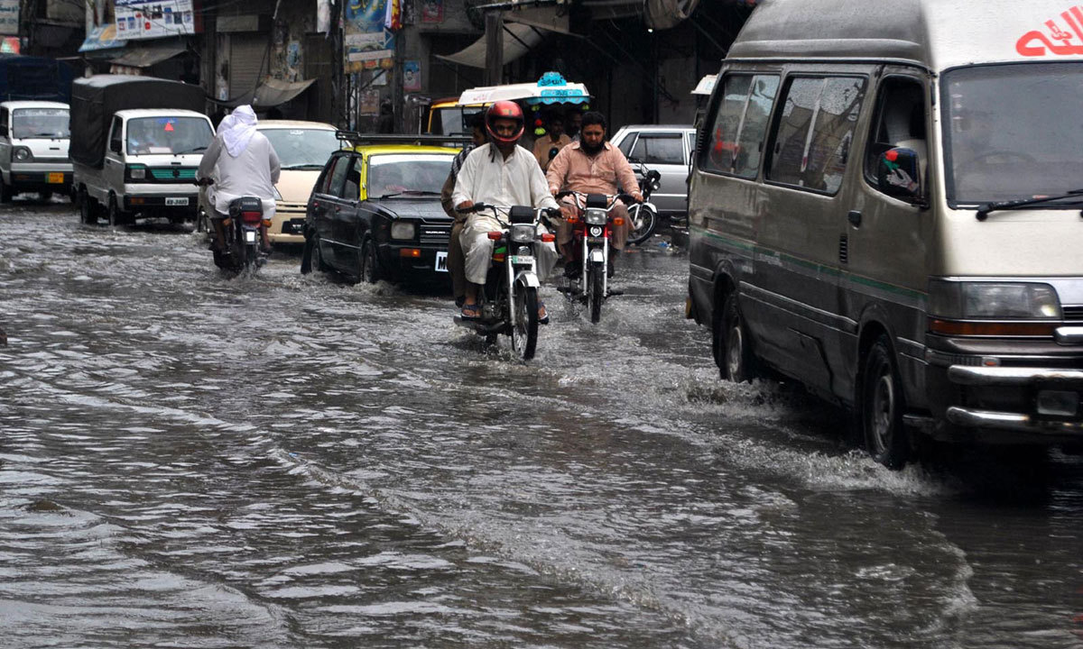 RAWALPINDI: Vehicles passing through the stagnant rain water after rain. — Photo by INP
