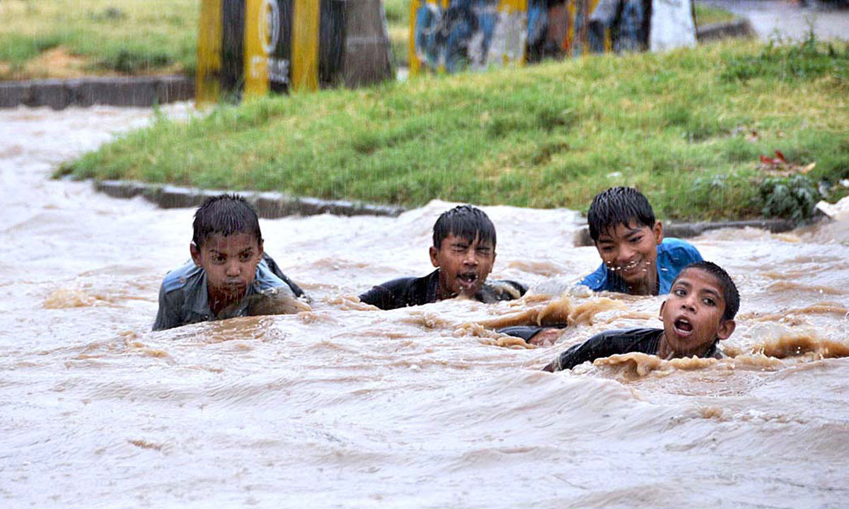 ISLAMABAD: Youngsters enjoying in the stagnant rain water after rain in federal capital city. — Photo by APP