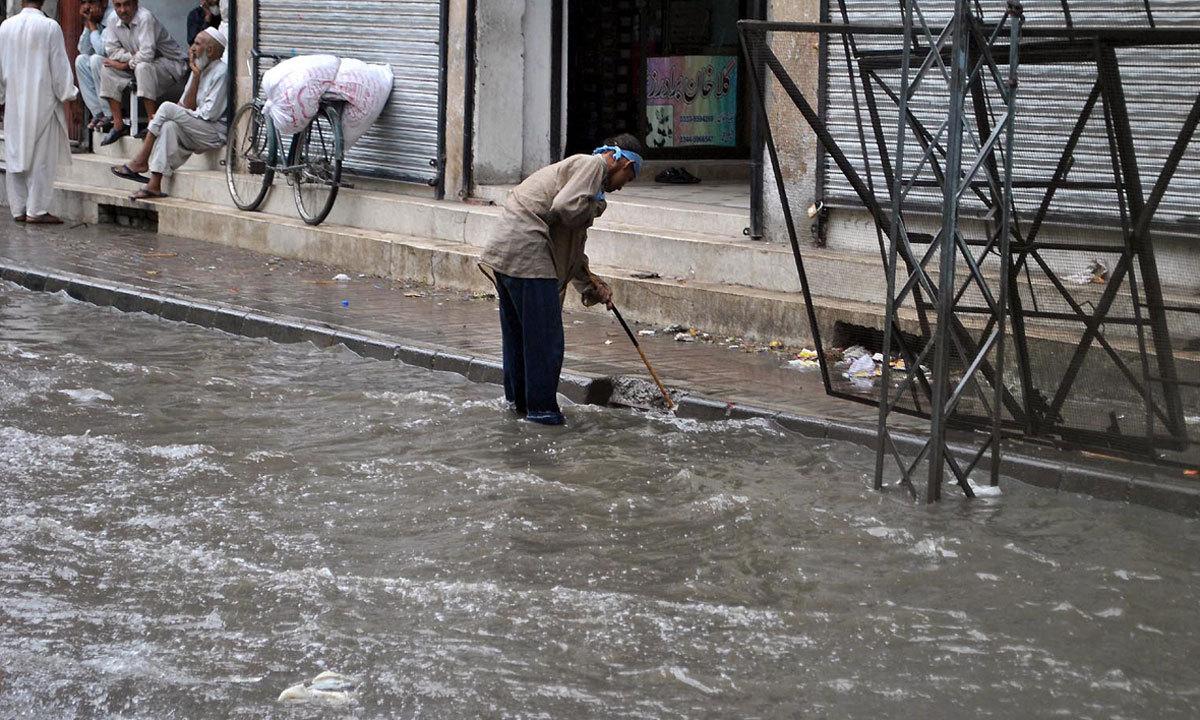 RAWALPINDI: Worker draining out stagnant rainwater at Jamia Masjid road. — Photo by INP