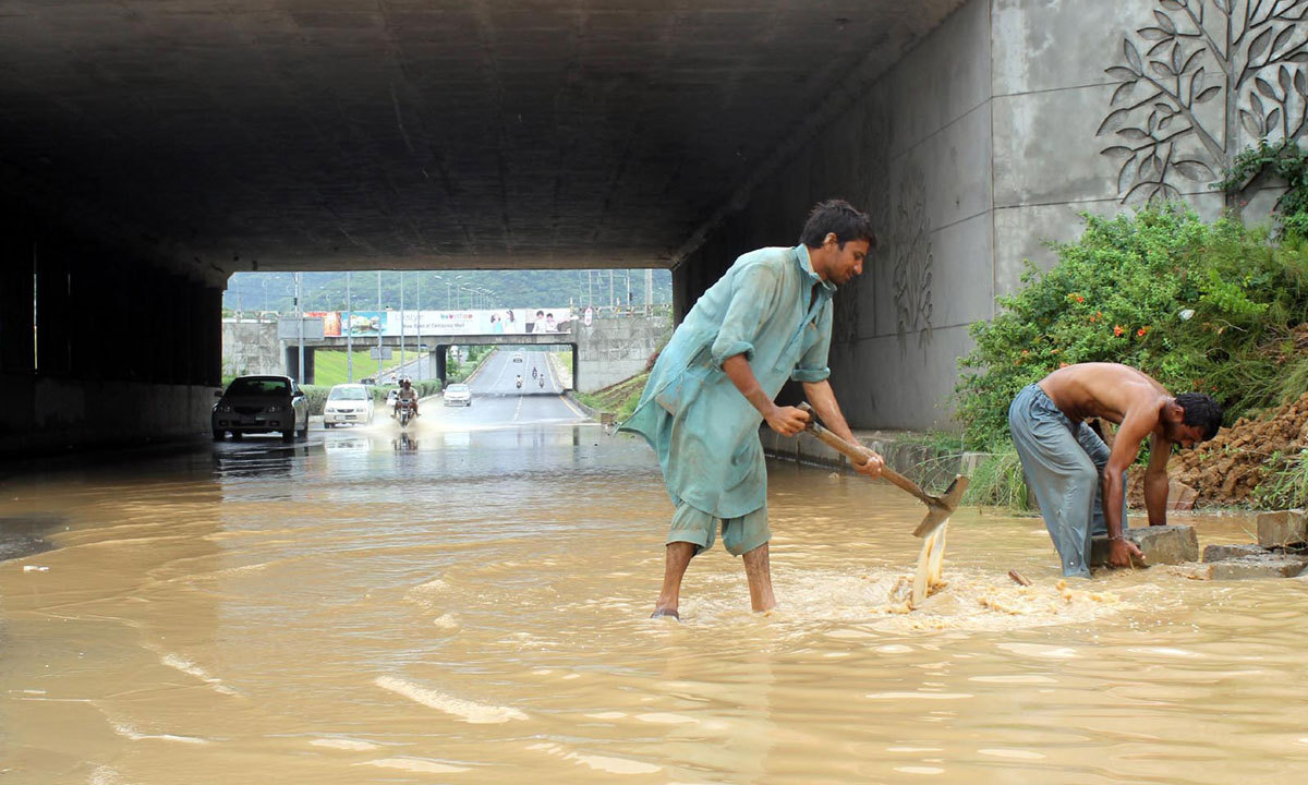 ISLAMABAD: Workers draining out stagnant rain water from 7th Avenue Underpass after heavy rain in morning. — Photo by INP