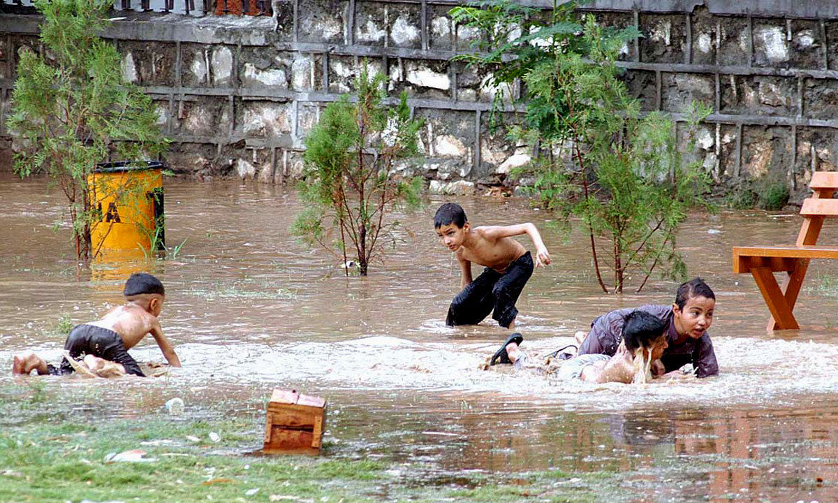 ISLAMABAD: Youngsters playing in stagnant water in a local park after rain in federal capital city. — Photo by APP