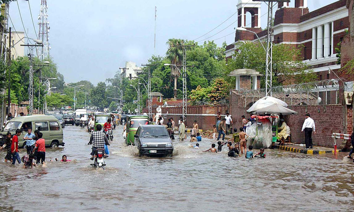 LAHORE: Children playing in rain water accumulated on road after heavy rain in provincial capital. — Photo by APP