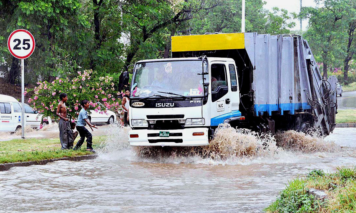ISLAMABAD: A vehicle passing through the stagnant rain water after rain in federal capital city. — Photo by APP