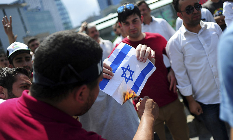 Pro-Palestinian demonstrators set fire to an image of an Israeli flag. — REUTERS