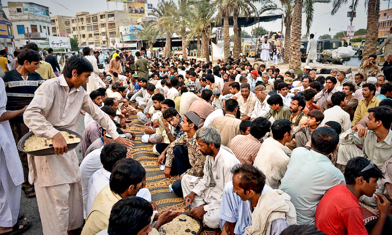 KARACHI: Workers of a charity dish out food for Iftari near Numaish Chowrangi on Monday.—Fahim Siddiqi/White Star