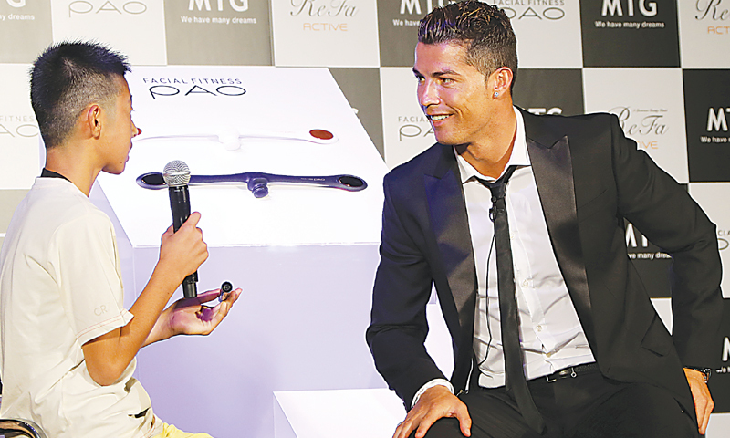 """TOKYO: Cristiano Ronaldo talks with a young Japanese fan during a promotional event titled  """"MTG x Cristiano Ronaldo, Athletic Beauty Project"""" on Tuesday.—AP"""