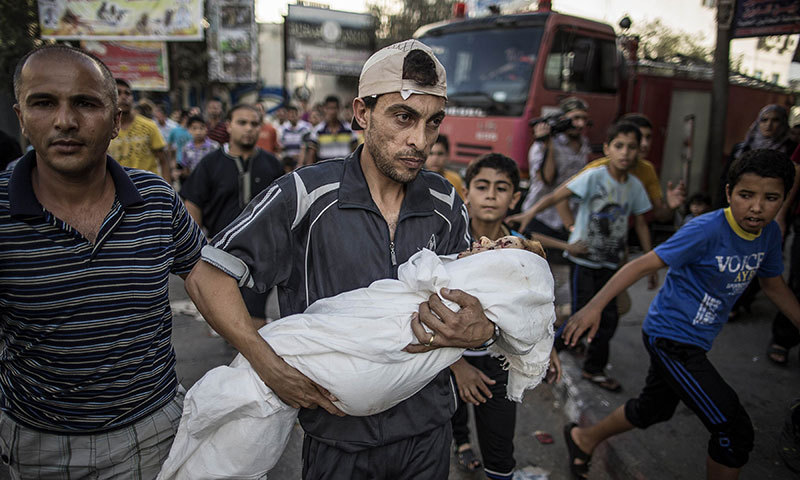 A relative of two-year old Palestinian Salma Radiya who was killed by shrapnel from an Israeli tank shell in the north of the Gaza Strip holds her body in the street outside the morgue of the Kamal Adwan hospital in Beit Lahia on July 23, 2014. – AFP