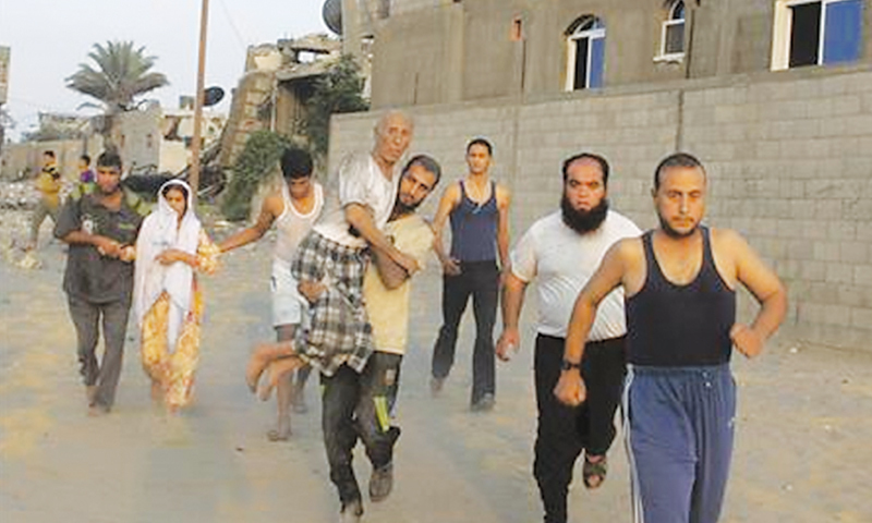 A Palestinian man carries his father as he and others run for cover during an Israeli air strike here on Wednesday.—AP