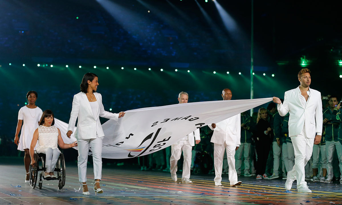 The Commonwealth Games flag is carried into the arena by former athletes including Australian swimmer Ian Thorpe, right, during the opening ceremony for the Commonwealth Games 2014 in Glasgow, Scotland, Wednesday, July 23, 2014. — Photo by AP