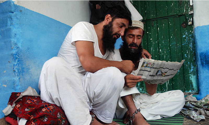 This photograph  shows chained drug addicts as they read a newspaper at a healing centre run by local cleric Ilyas Qadri, the so-called spiritual healer of drug addicts in Haripur, some 70 kilometres north of Islamabad. — Photo by AFP
