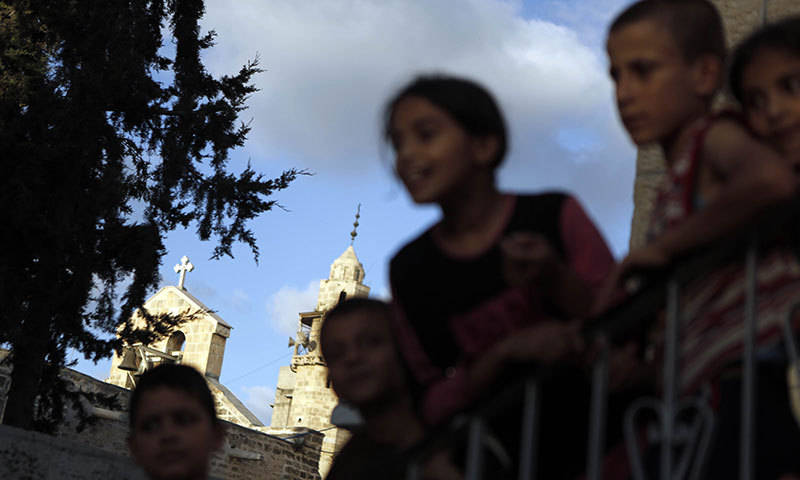 Displaced Palestinian children stand at the stairs of a Greek Orthodox church where many Palestinians are taking shelter in Gaza City on July 25, 2014. — Photo by AFP