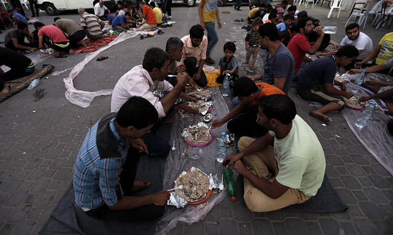Displaced Palestinian gather of Iftar meal at a Greek Orthodox church where many Palestinians are taking shelter in Gaza City on July 25, 2014. — Photo by AFP