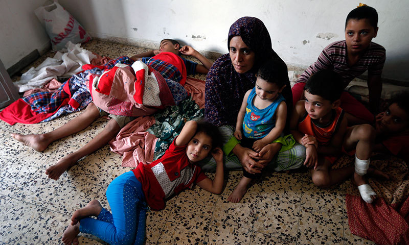 A Palestinian family sits inside the St. Porphyrios Church in Gaza City where many Palestinians have sought refuge from the war, on Wednesday, July 23, 2014. — Photo by AP
