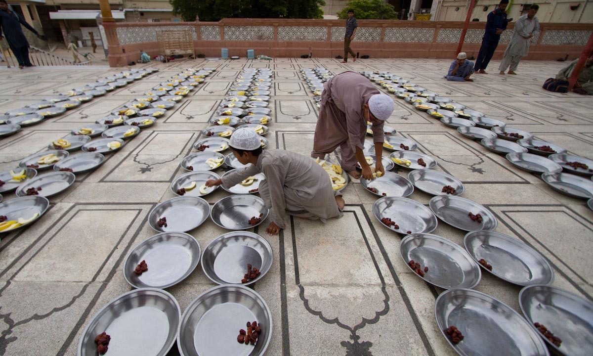 Volunteer boys place fruits in dishes for Iftar.