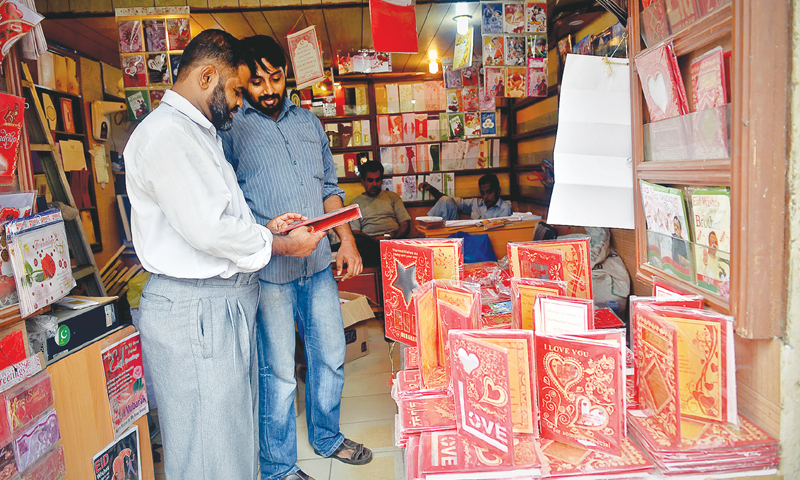 Customers carefully selecting Eid cards in a shop at Pakistan Chowk.—White Star