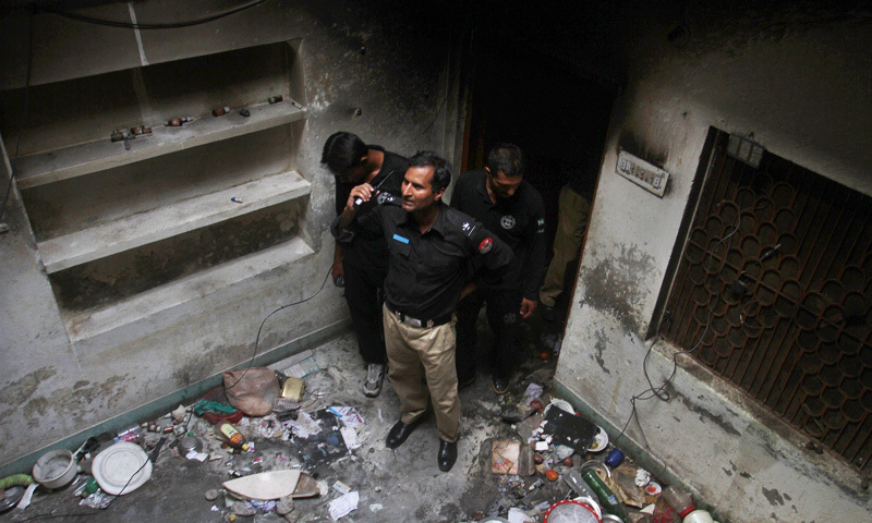 Police officers examine a house of a family belonging to the Ahmadi community, which was torched by an angry mob in Gujranwala. -Photo by AP
