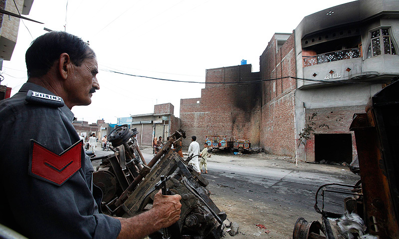 A policeman sits near damaged machine parts, in front of a house that was burned by an angry mob on Sunday night, in Gujranwala. -Photo by Reuters