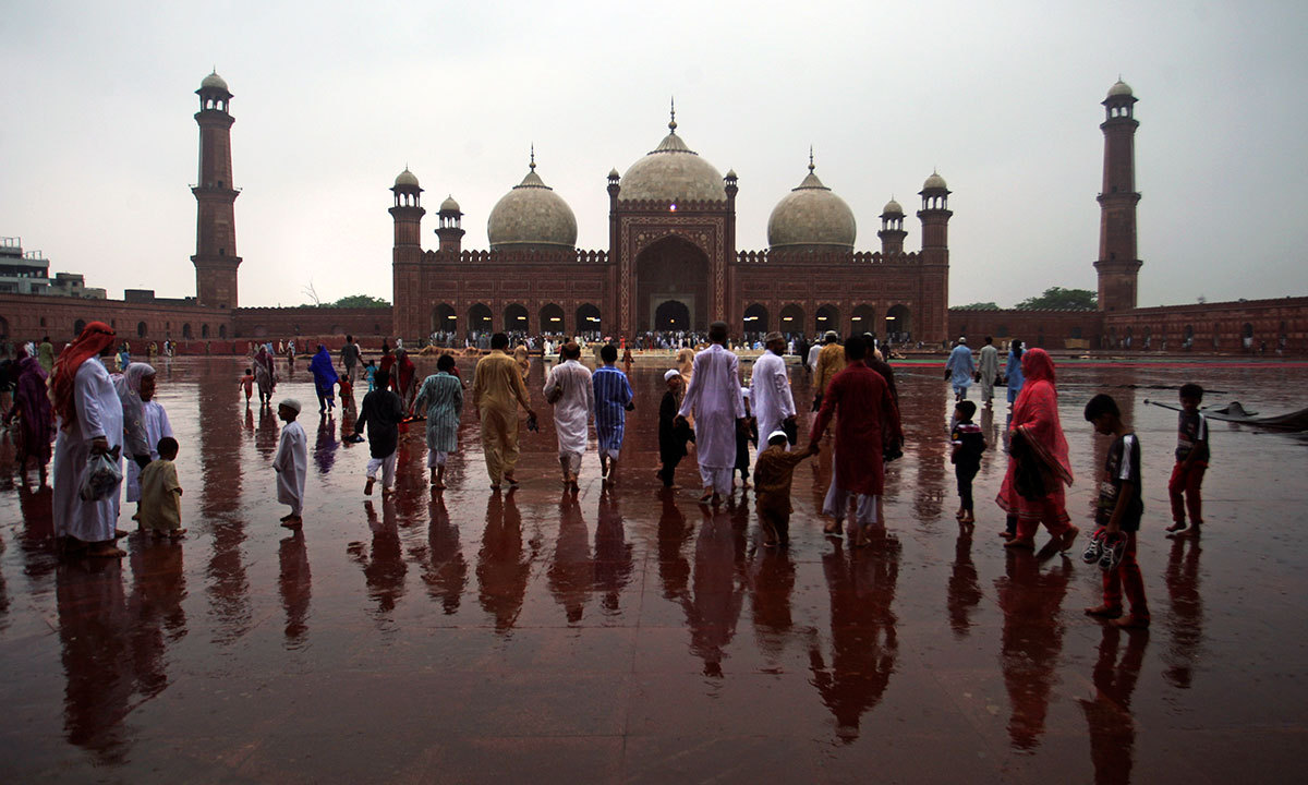 Pakistani Muslims walk towards the Badshahi mosque to offer the Eidul Fitr prayer at the beginning of a major holiday marking the end of the fasting month of Ramazan in Karachi, Pakistan, Tuesday, July 29, 2014.— Photo by AP