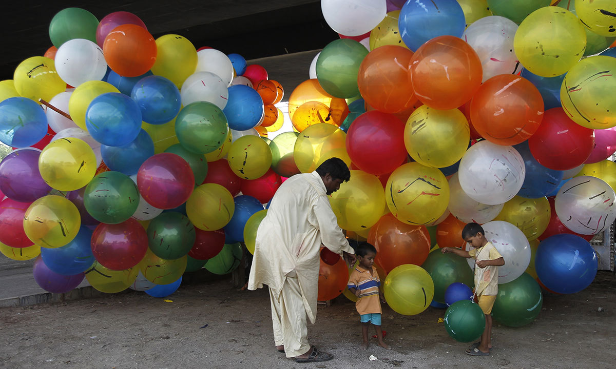 Pakistani children buy balloons to celebrate the Muslim Eid holiday marking the end of the fasting month of Ramzan in Karachi, Pakistan, Tuesday, July 29, 2014. — Photo by AP