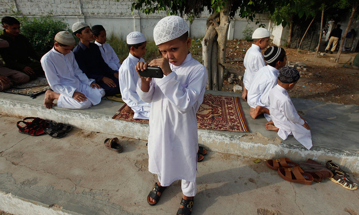 A boy reacts to the camera as he takes picture with his mobile phone camera while others attend attend Eidul Fitr prayers at Karachi's railway grounds July 29, 2014. — Photo by Reuters