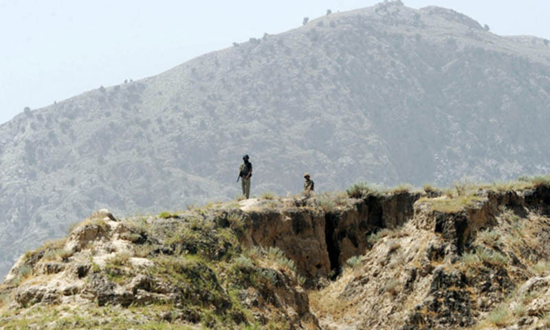 This file photo shows a Pakistani soldiers standing guard on a mountain ridge near the Pak-Afghan border.  — File photo by AFP
