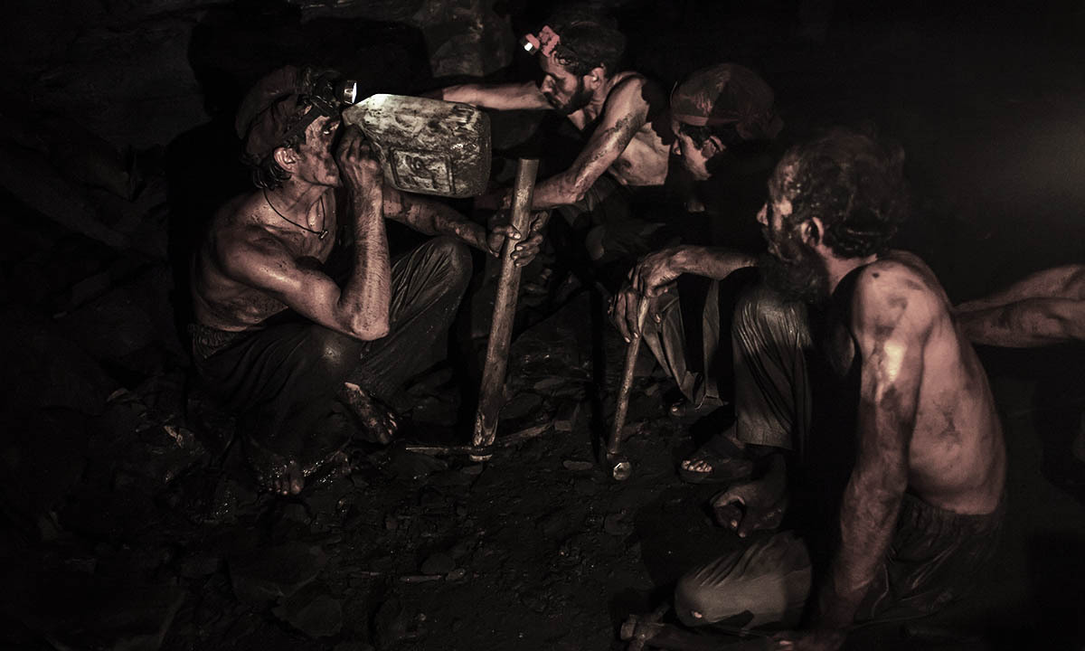 Miners take a break to drink water inside a coal mine in Choa Saidan Shah, Punjab province, April 29, 2014. — Photo by Reuters