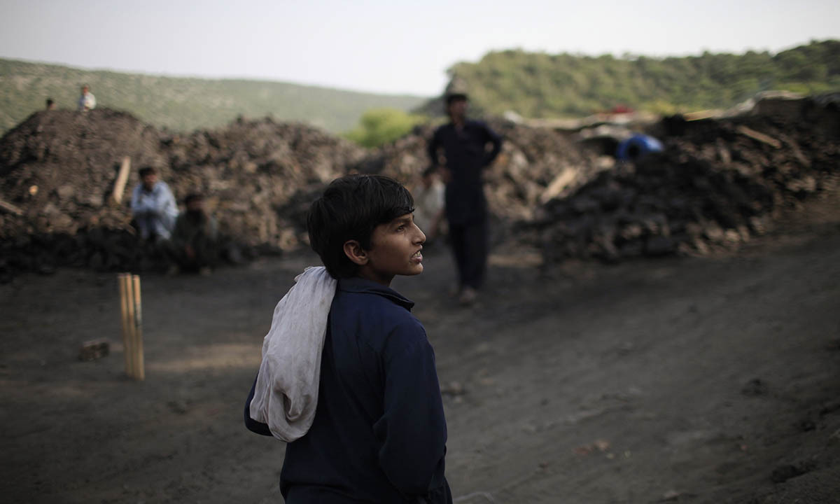 Samiullah watches the other miners play cricket at a coal field in Choa Saidan Shah, Punjab province, May 5, 2014.  — Photo by Reuters