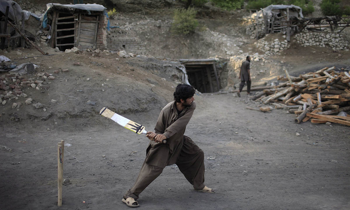 A miner plays cricket in the evening at a coal field in Choa Saidan Shah, Punjab province, May 5, 2014.  — Photo by Reuters