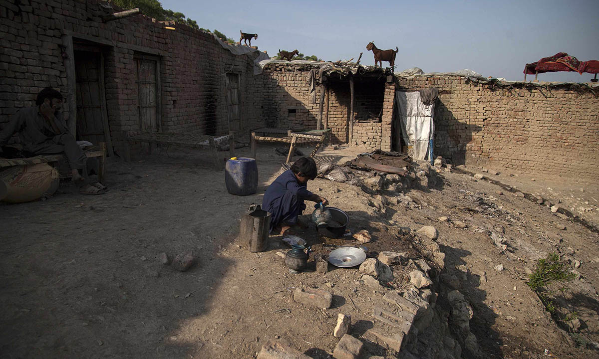 Samiullah, who claims to be 14-years-old,washes dishes at a coal mine in Choa Saidan Shah, Punjab province, May 5, 2014.  — Photo by Reuters