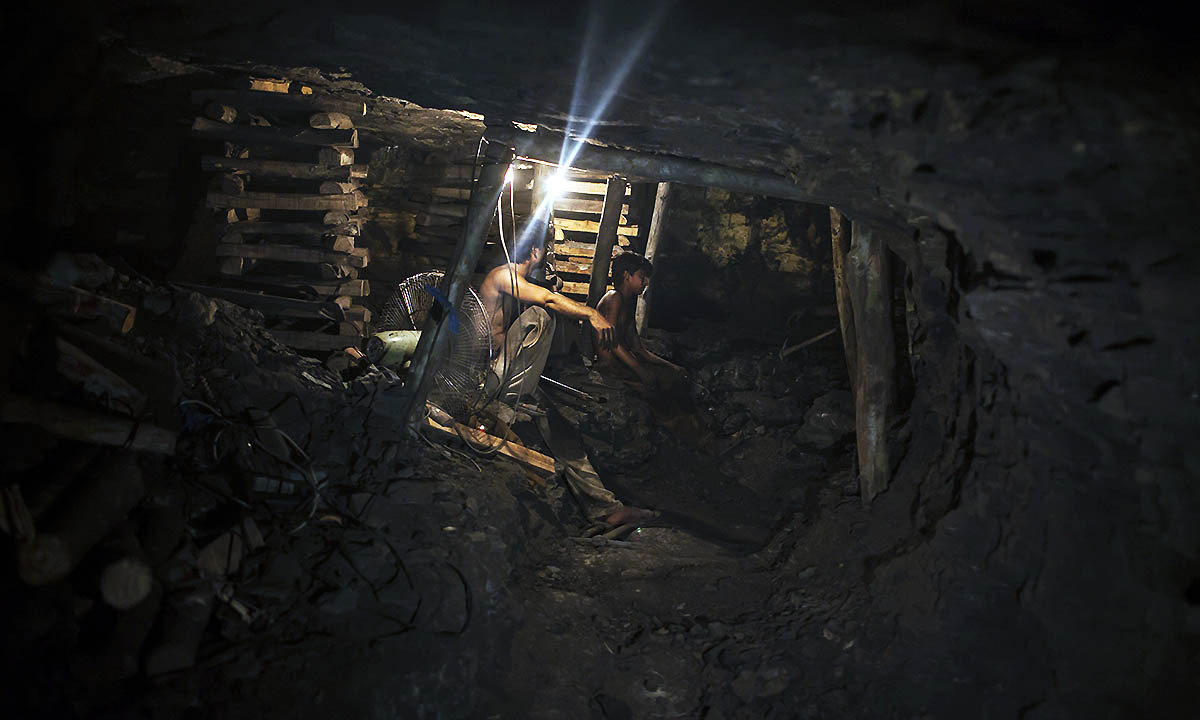 Samiullah, who says he is 14-years-old, sits at the coal face to observe the process of coal mining, underground in Choa Saidan Shah, Punjab province, April 29, 2014.  — Photo by Reuters