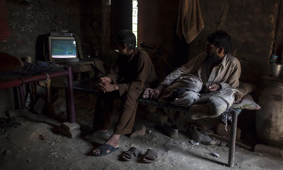 Miners watch TV in a room at a coal field in Choa Saidan Shah, Punjab province, May 5, 2014.  — Photo by Reuters