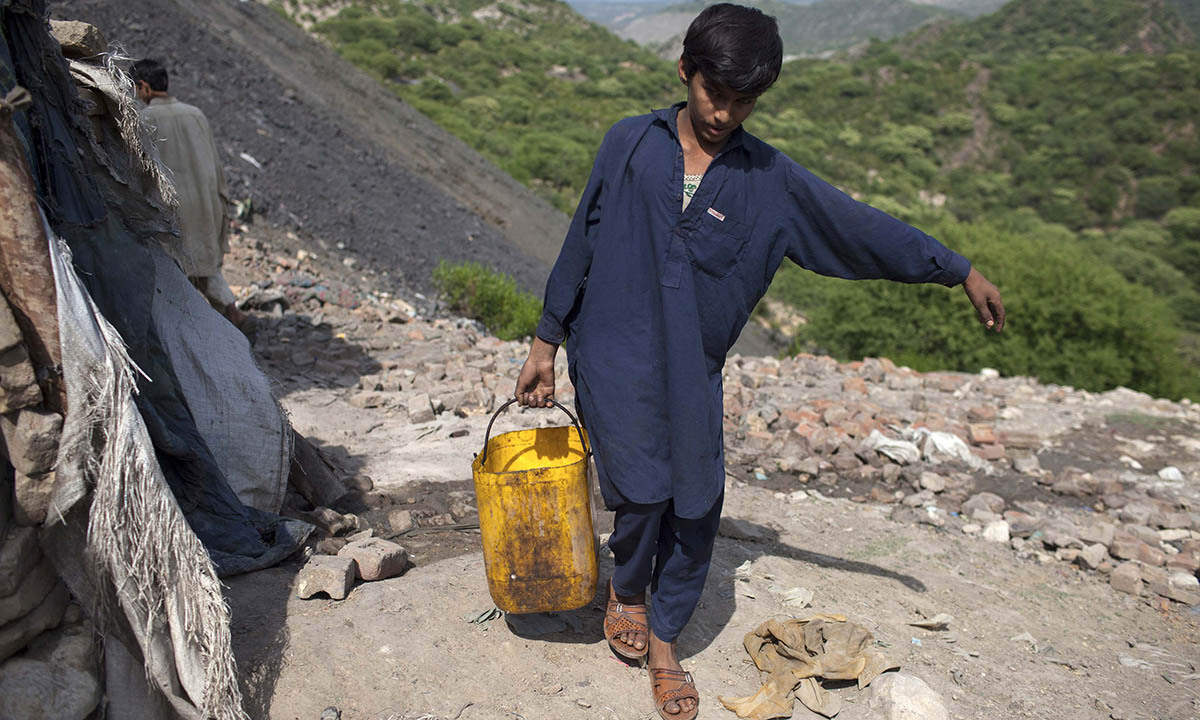 Samiullah carries water for his uncle's bath at a coal field in Choa Saidan Shah, Punjab province, May 5, 2014.  — Photo by Reuters