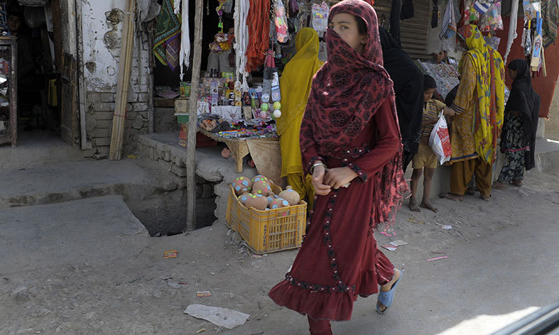 Female pedestrian as she walks through a market in Quetta, the site of an acid attack on female pedestrians. — Photo by AFP