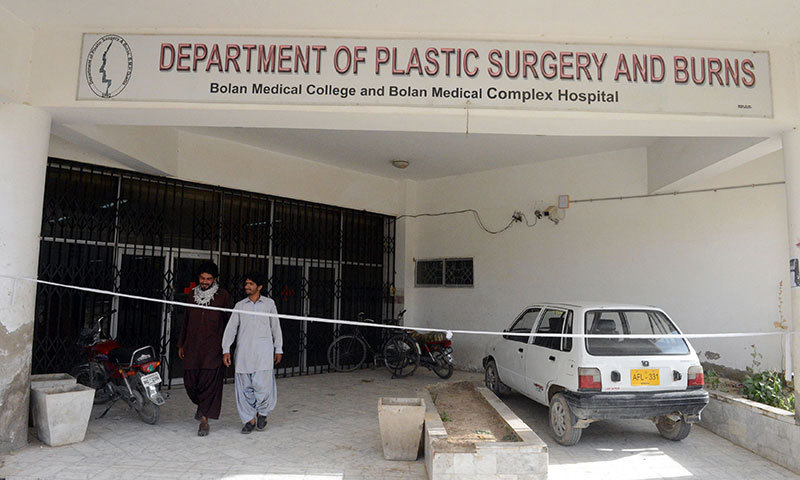 Pedestrians as they walk at the entrance of the Department of Plastic Surgery and Burns of Bolan Medical Complex in Quetta, which was cordoned off by the hospital administration where female acid victims were under treatment. — Photo by AFP