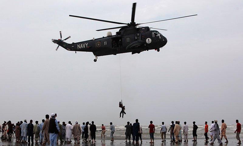 People gather as a Pakistan Navy diver attached to a sling rope from a helicopter, holds the body of a man who had drowned on Wednesday, after recovering it from Arabian Sea during a search rescue operation at Karachi