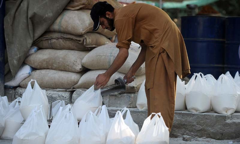 A Pakistani worker prepares bags of wheat flour. AFP file photo