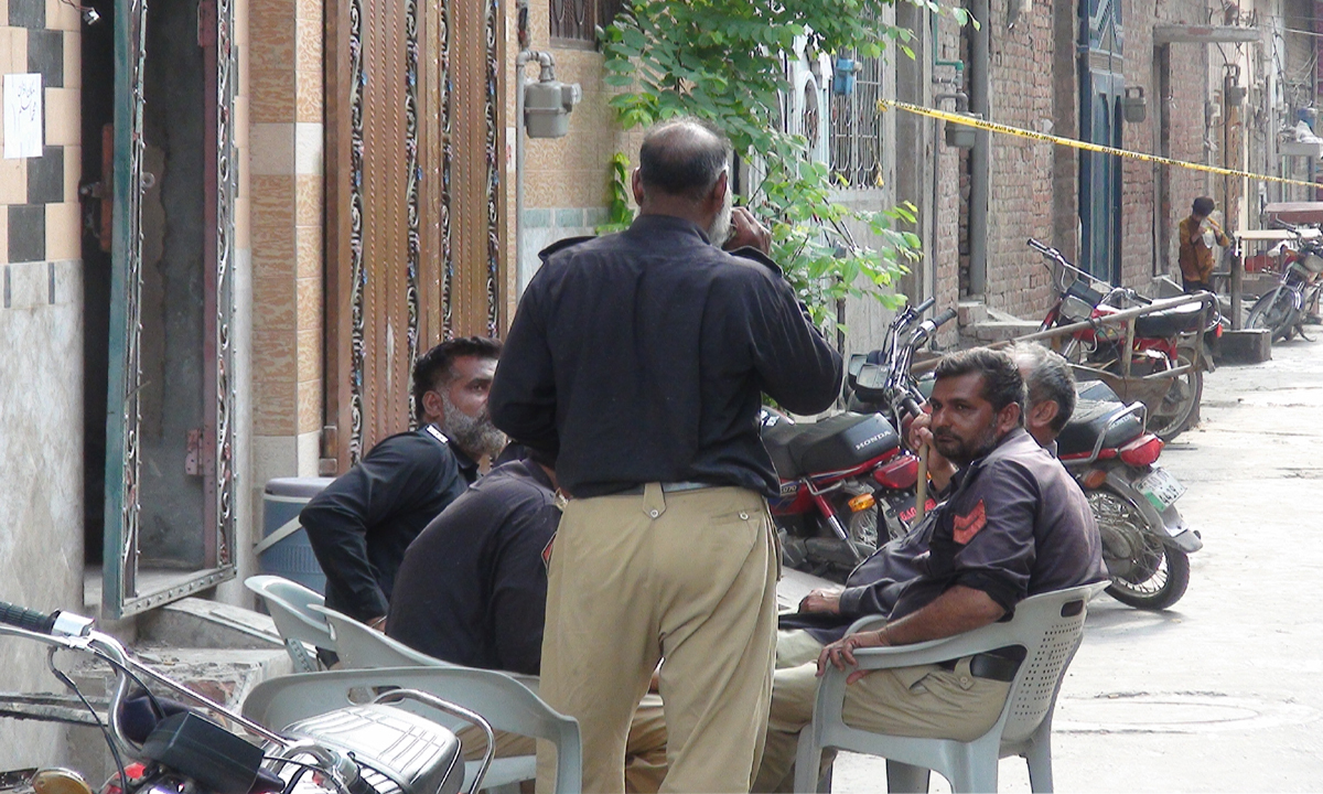 Policemen are deployed outside the torched homes of Ahmadis living in People's Colony