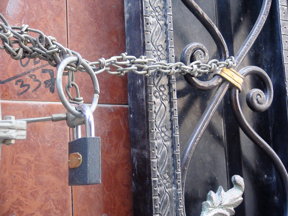 Photo shows a padlocked gate at the home of one People