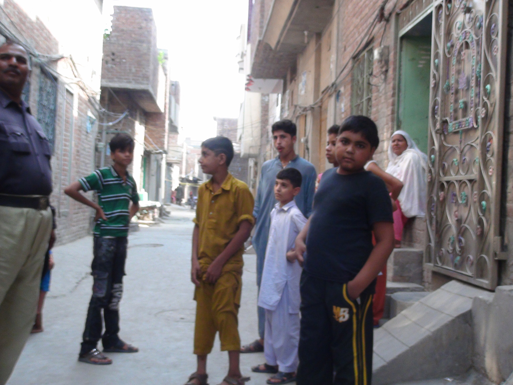 Children stand in  in the People's Colony, where an angry mob burnt down the homes of five members of the Ahmadi community