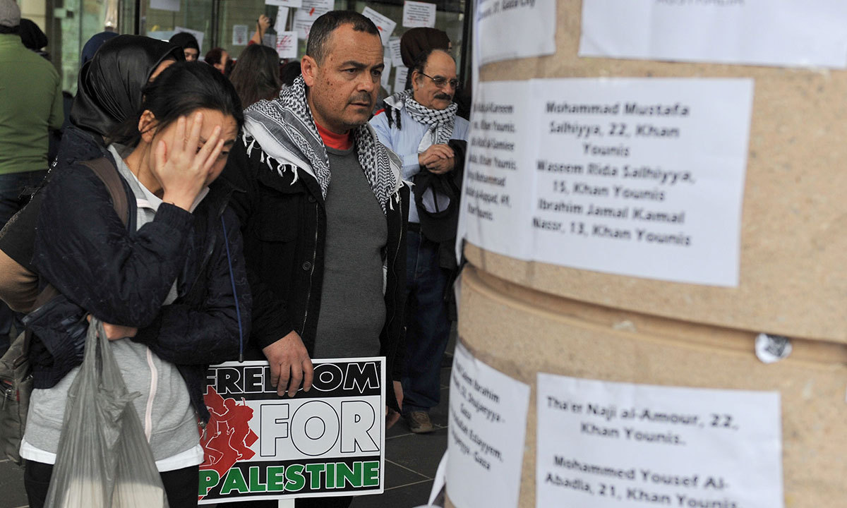 People read the names and stories of Palistinian victims killed in Gaza on the Department of Foreign Affairs building during a march in support of the Global Day of Rage against Israel's actions in Gaza in Melbourne. AFP