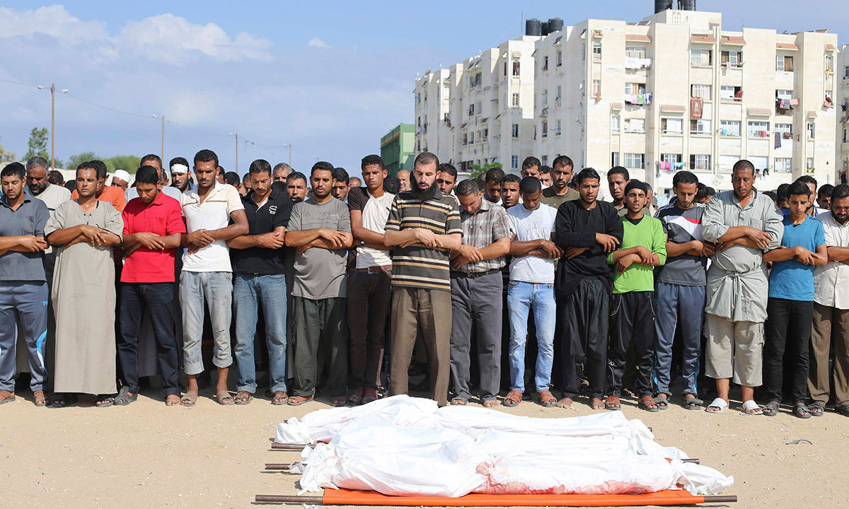Palestinians pray next to the bodies of three members of Abu Hadaf family, whom medics said were killed by an Israeli air strike. REUTERS