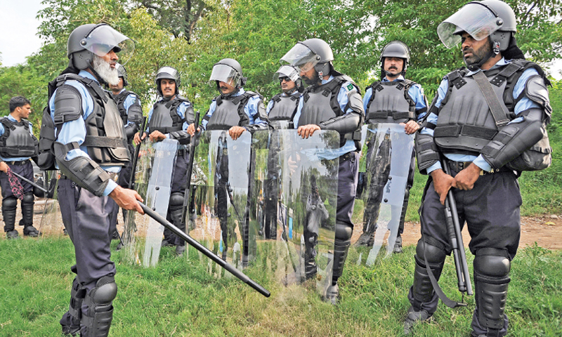 Capital police personnel in riot gear stand on a greenbelt in Islamabad on Saturday — Photo by Tanveer Shahzad
